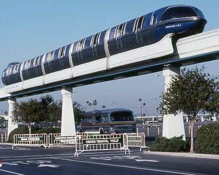 blue monorail travelling over parking lot
